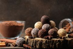 Assorted chocolates. candy balls of different types of chocolate on a brown wooden table. cinnamon and cocoa stock photography
