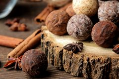 Assorted chocolates. candy balls of different types of chocolate on a brown wooden table. cinnamon and cocoa royalty free stock photos