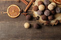 Assorted chocolates. candy balls of different types of chocolate on a brown wooden table. cinnamon and cocoa. top view stock image