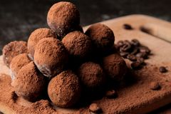 Assorted chocolates. candy balls of different types of chocolate on a dark background. cocoa and coffee beans royalty free stock image