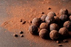 Assorted chocolates. candy balls of different types of chocolate on a dark background. cocoa and coffee beans royalty free stock images