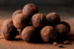 Assorted chocolates. candy balls of different types of chocolate on a dark background. cocoa and coffee beans royalty free stock photos