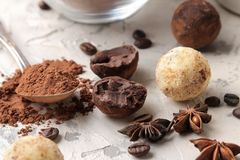 Assorted chocolates. Candy balls of different types of chocolate on a light concrete background. cocoa, star anise and coffee bean. S stock image