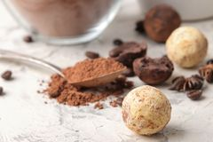 Assorted chocolates. Candy balls of different types of chocolate on a light concrete background. cocoa, star anise and coffee bean. Assorted chocolates. Candy stock photography