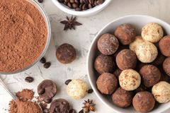 Assorted chocolates. Candy balls of different types of chocolate on a light concrete background. cocoa, star anise and coffee bean. S. top view royalty free stock photography
