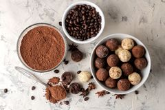 Assorted chocolates. Candy balls of different types of chocolate on a light concrete background. cocoa, star anise and coffee bean. S. top view stock images