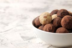 Assorted chocolates. Candy balls of different types of chocolate on a light concrete background. free space royalty free stock photos
