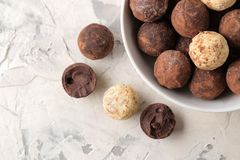 Assorted chocolates. Candy balls of different types of chocolate on a light concrete background. top view stock image