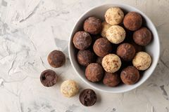 Assorted chocolates. Candy balls of different types of chocolate on a light concrete background. top view stock images