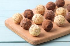 Assorted chocolates. Candy balls of different types of chocolate on a wooden board on a blue wooden table royalty free stock photos