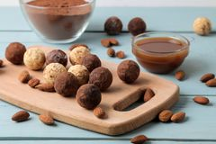 Assorted chocolates. Candy balls of different types of chocolate on a wooden board on a blue wooden table. Caramel, Almond and Coc. Oa stock images