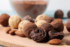 Assorted chocolates. Candy balls of different types of chocolate on a wooden board on a blue wooden table. almond and cocoa stock photo