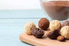 Assorted chocolates. Candy balls of different types of chocolate on a wooden board on a blue wooden table. almond and cocoa royalty free stock photos