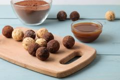 Assorted chocolates. Candy balls of different types of chocolate on a wooden board on a blue wooden table. Caramel and Cocoa stock photo