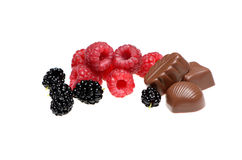 Assorted chocolates with raspberries and mulberries Royalty Free Stock Photography