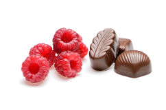 Assorted chocolates with raspberries on the white background Stock Images