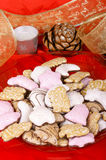 Assorted Christmas gingerbread cookies. On a red plate and Christmas decorations over a red background Stock Photo