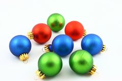 Assorted Christmas Ornaments. Eight green, red, and blue Christmas tree ornaments scattered on a white background Stock Image