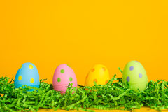 4 assorted color Easter eggs on a bright yellow ba Royalty Free Stock Photo