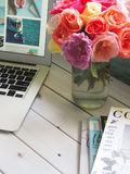 Assorted-color Flower Arrangement in Clear Glass Vase Beside a Laptop Royalty Free Stock Photo