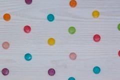 Assorted coloreó los caramelos en la tabla de madera blanca Imagen de archivo