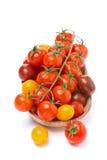 Assorted coloreó los tomates de cereza en el cuenco de madera, aislado Foto de archivo libre de regalías