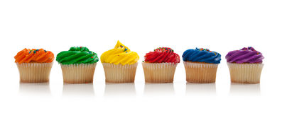 Assorted colored Cupcakes with sprinkles on white