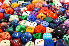 Assorted Colorful Dice Background. A collection of assorted dice in several colors and a variety of shapes and sizes Stock Photography