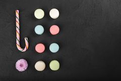 Assorted colorful french macarons and christmas lollipop on a black background. Space for text, closeup, top view stock image