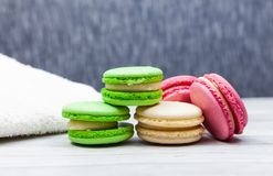 Assorted colorful macaroons on blue background, next to white towel royalty free stock photo