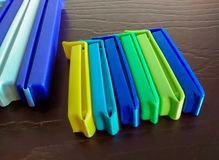 Assorted colorful plastic clips for closing bags. These colorful plastic clips for closing bags are laid in a row on a brown wooden table Royalty Free Stock Images