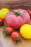 Assorted colorful  wet tomatoes. On wooden board Stock Photo