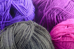 Assorted Colors of Rolled Yarn. Close up Assorted Colors of Rolled Yarn. Emphasizing, Gray, Violet, Purple and Red Violet Colors Royalty Free Stock Images