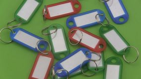 Assorted coloured  key tags rotating on a green background. Stock Photos