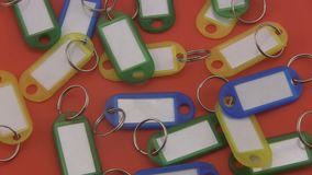 Assorted coloured  key tags rotating on a red background. stock video