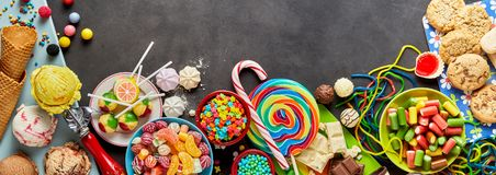 Assorted colourful confectionery with copy space. An assortment of colourful, festive sweets, ice-cream and candy in a panoramic orientation with a dark Stock Images