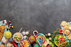 Assorted colourful, festive sweets with copy space. An assortment of colourful, festive sweets, ice-cream and candy on a dark, rustic background with copy space Royalty Free Stock Images