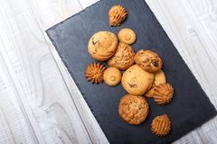 Assorted cookies with chocolate chip, oatmeal raisin on stone slate background on wooden background close up. stock photo