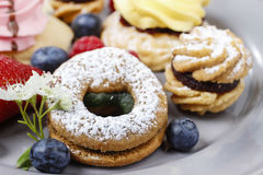 Assorted cookies and fruits on grey ceramic plate Royalty Free Stock Images