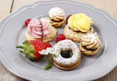 Assorted cookies and fruits on grey ceramic plate Royalty Free Stock Photo