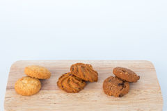 Assorted cookies on wooden boards White background and wheat. Chocolate chip cookies, Raisin cookies, Coconut cookies stock image
