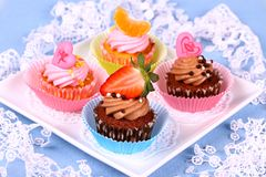 Assorted cup cakes with angel, heart, tangerine, strawberry Royalty Free Stock Photography