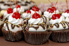Assorted Cupcakes on Display. Banana split chocolate cupcakes topped with cherries sitting on display table Stock Images