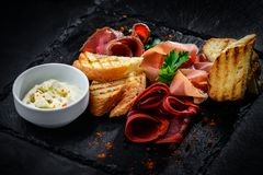 Assorted Deli Cold Meats on a plate. Assorted Cold Deli Meats on a plate with sauce on the black tiles Stock Image