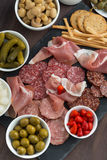 Assorted deli meat snacks, sausages and pickles on a blackboard Royalty Free Stock Images