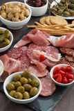Assorted deli meat snacks, sausages and pickles on a blackboard Stock Photography
