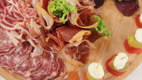 Assorted deli meats, ham, salami, bacon on the wood tray stock footage