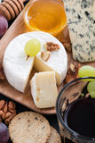 Assorted delicatessen appetizers - cheeses, grapes, crackers Royalty Free Stock Image