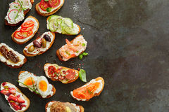 Assorted delicious fresh canapes. With seafood, vegetable and meat toppings arranged to the side on textured granite or slate with copy space, overhead view Stock Image