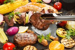 Assorted delicious grilled barbecue meat with vegetable. Beef gr. Illed steaks with spicy sausages, beef kebabs, corn, cherry tomato,  pepper, slices of onion Royalty Free Stock Images